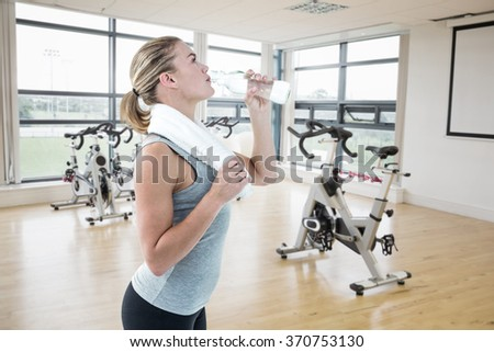 Fit woman drinking water against spinning exercise bikes in gym room - stock photo