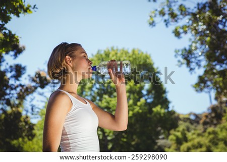 Fit woman drinking water in park on a sunny day - stock photo