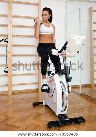 fit woman driving stationary bicycle and working with weights in gym - stock photo