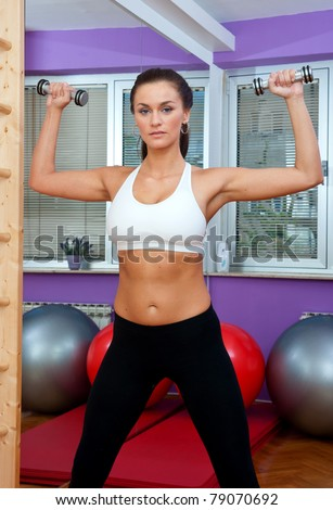 fit woman exercise in fitness studio with weights - stock photo