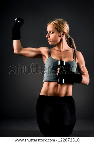 Fit woman exercising with weights