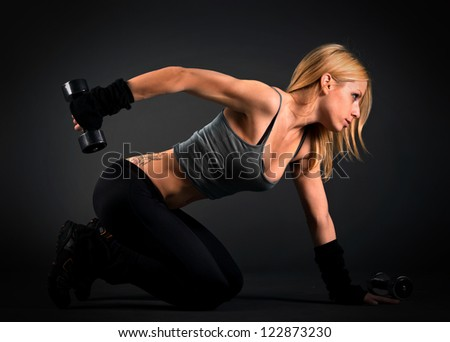 Fit woman exercising with weights - stock photo