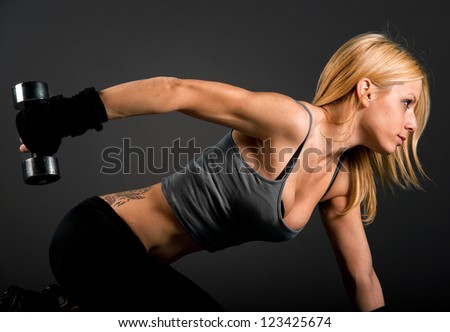Fit woman exercising with weights over a dark background - stock photo