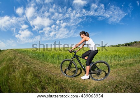 Fit woman going for bike ride on a sunny day in the countryside