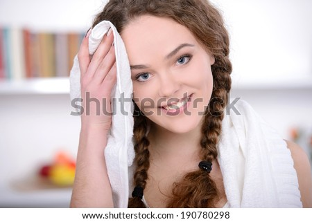 Fit woman holding a towel on her shoulder after workout at home - stock photo