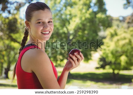 Fit woman holding bag of healthy groceries on a sunny day - stock photo