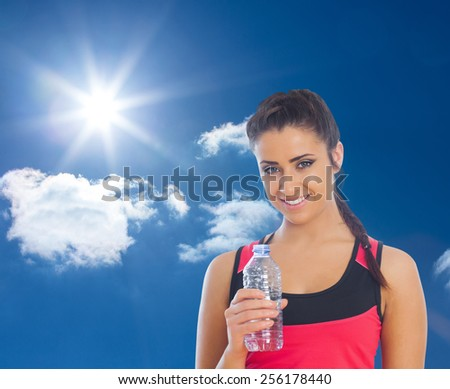Fit woman holding water bottle against bright blue sky with clouds