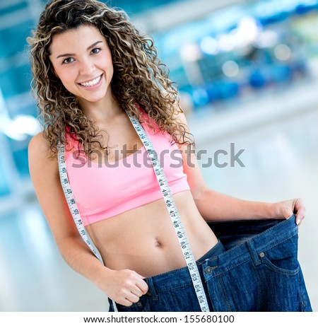 Fit woman in big pants after loosing a lot of weight  - stock photo