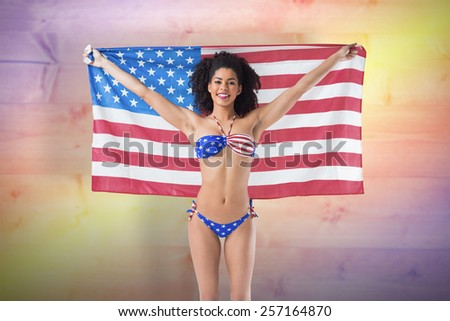 Fit woman in bikini against yellow and purple planks - stock photo