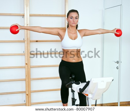 fit woman in fitness salon exercise on stationary bike - stock photo