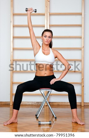 fit woman in fitness salon exercise with weights - stock photo
