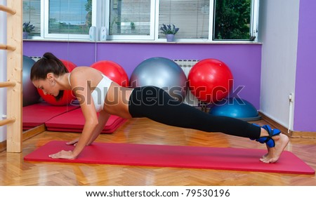 fit woman in fitness salon in push up pose exercise - stock photo