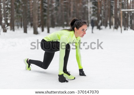 Fit woman in position ready to run outdoors winter park - stock photo