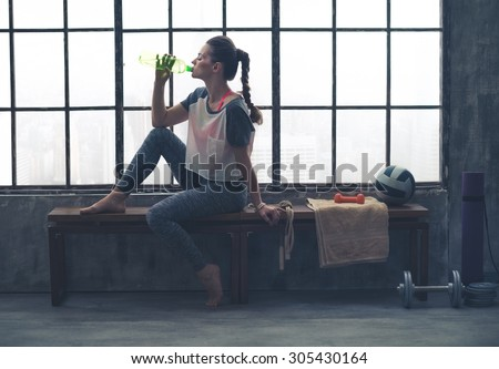 Fit woman in profile sitting on bench in loft gym drinking water. After a good workout, it's important to hydrate. - stock photo