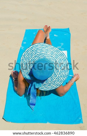 Fit woman in sun hat and bikini at the  beach