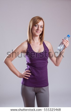 Fit woman is holding a bottle with water on a grey background