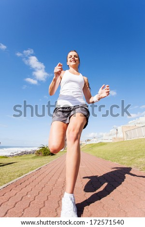 fit woman jogging at the beach - stock photo