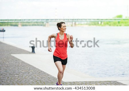Fit woman jogging by the river. - stock photo