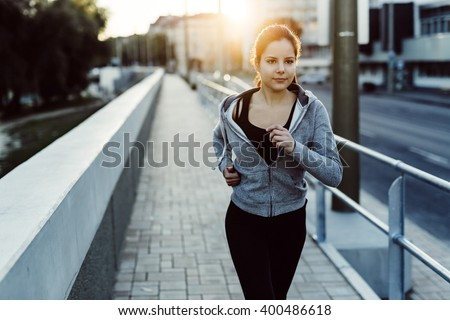 Fit woman jogging in city in beautiful sunset - stock photo