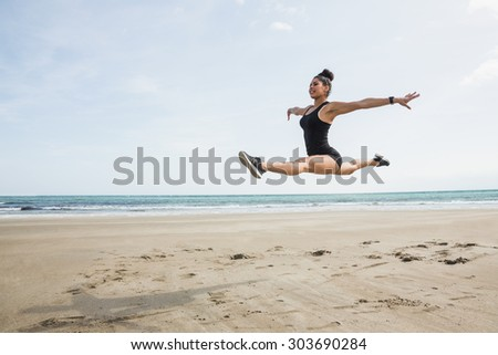 Fit woman leaping on the sand at the beach - stock photo