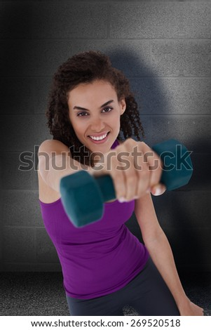 Fit woman lifting blue dumbbell against dark grey room - stock photo