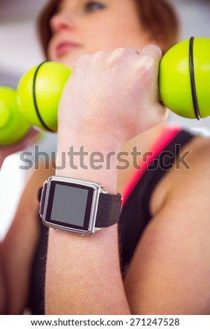 Fit woman lifting dumbbell sitting on ball at home in the living-room - stock photo