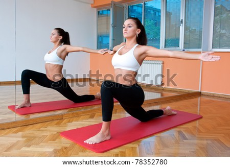 fit woman making stretching exercise in front of fitness studio mirror