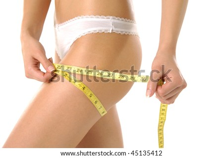 Fit woman measuring her waist after exercisin
