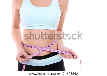 Fit woman measuring her waist after exercising
