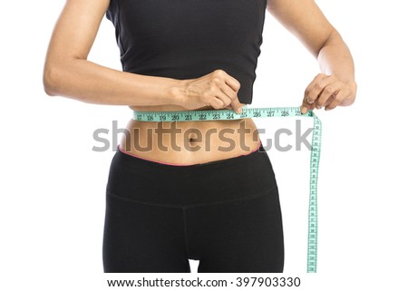 Fit woman measuring her waist over a white background - stock photo