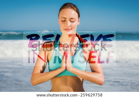 Fit woman meditating on the beach against believe in myself - stock photo