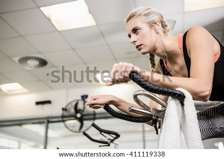 Fit woman on exercise bike at the gym - stock photo