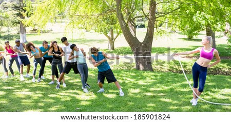 Fit woman playing tug of war with group of friends in the park - stock photo
