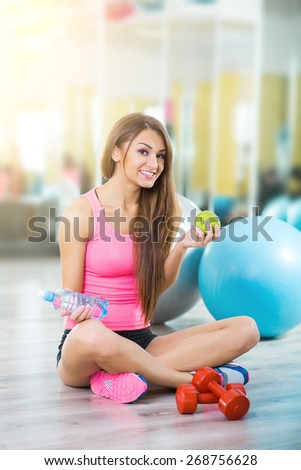 Fit woman refreshing after workout in gym - stock photo