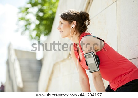 Fit woman rest after jogging and listening music.