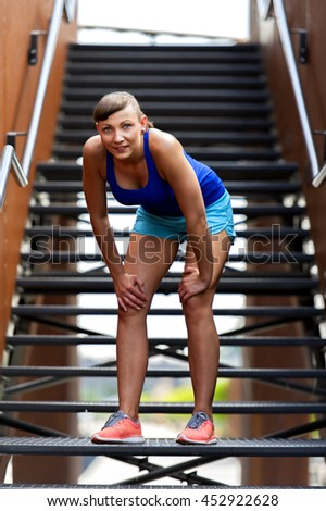 Fit woman resting after run on stairs smiling.