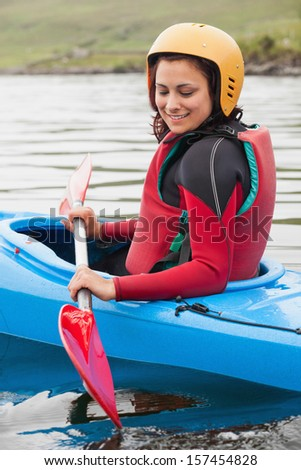 Fit woman rowing on lake in a kayak and smiling - stock photo