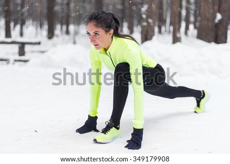 Fit woman runner stretching her muscles before training Winter park - stock photo
