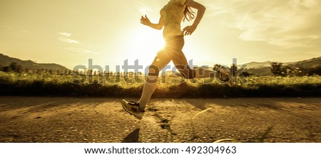 Fit woman running fast, training in bright sunshine