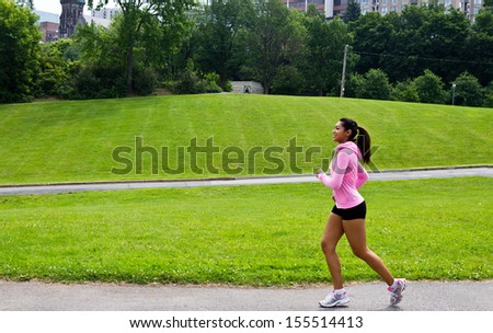 Fit woman running in the city park