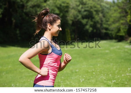Fit woman running in the sunshine and smiling outside in a park - stock photo