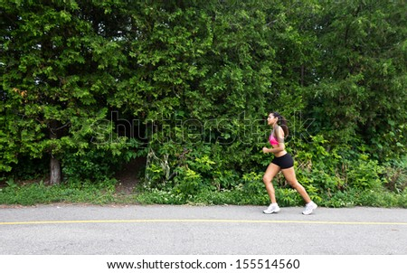Fit woman running on the nature trail - stock photo
