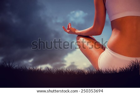 Fit woman sitting in lotus pose against blue sky over grass - stock photo