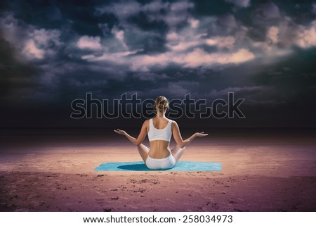 Fit woman sitting in lotus pose against dark cloudy sky