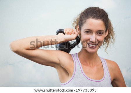 Fit woman smiling at camera holding kettlebell at the gym