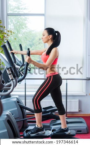 Fit woman sport exercising at the gym on an x-trainer cardio machine, fitness center - stock photo