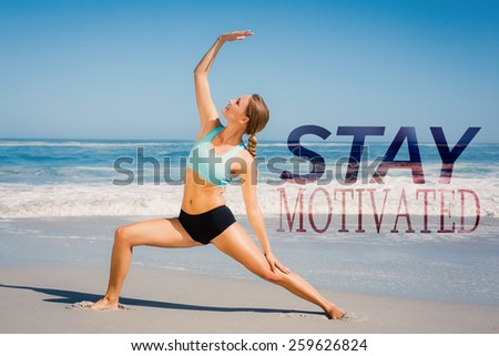 Fit woman standing on the beach in warrior pose against stay motivated - stock photo