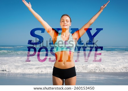 Fit woman standing on the beach with arms up against stay positive - stock photo