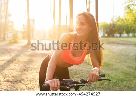 Fit woman standing with bicycle in park enjoying sunset