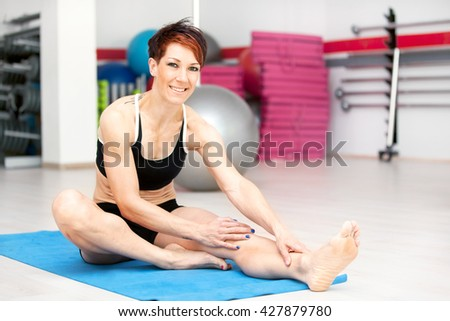 Fit woman stretching after workout at the gym